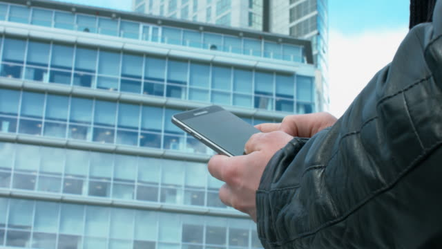 Man In Skin Coat Using His Mobile Next To Office Buildings video