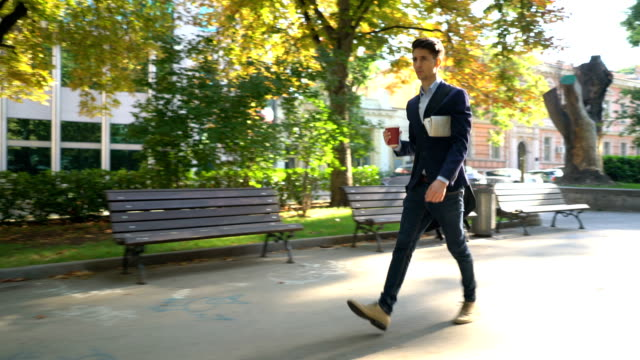 Man in smart casual clothing walking with cup of coffee in hand video