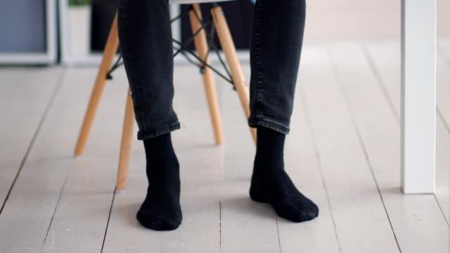 vidéos et rushes de homme dans des chaussettes marchant le rythme au lieu de travail sous la table - bureau ameublement