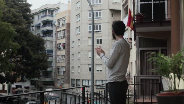 vídeos y material grabado en eventos de stock de hombre en españa aplaudiendo en el balcón en apoyo del personal médico que lucha contra el coronavirus - aplaudir
