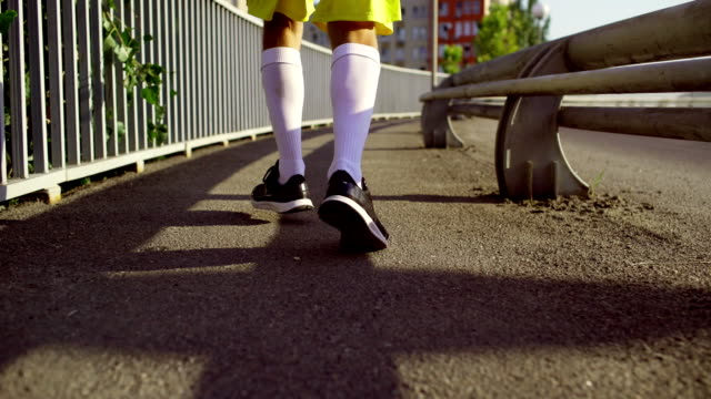 A man in sports clothes runs across the bridge in the morning video