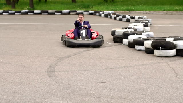 Man in suit driving Go-Kart car in racing track.