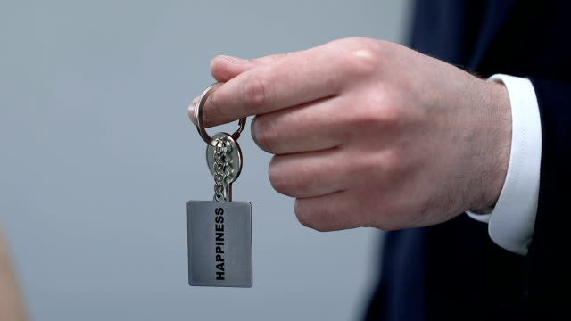 man in suit giving woman keychain with happiness word, motivation concept - key ring stock videos & royalty-free footage