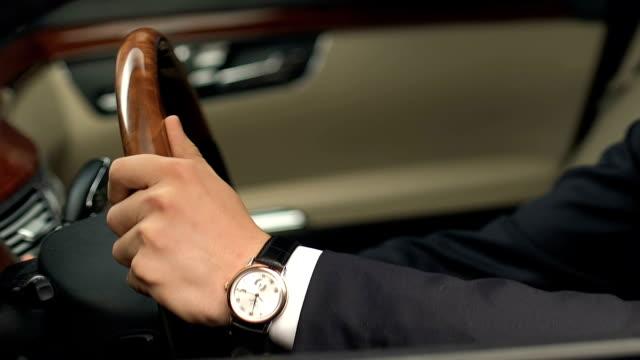 mann im anzug auf fahrer platz sitzen und halten lenkrad, neues auto zu kaufen - billionär stock-videos und b-roll-filmmaterial