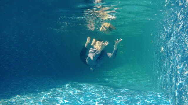 Man in suit tries to catch the book under water video
