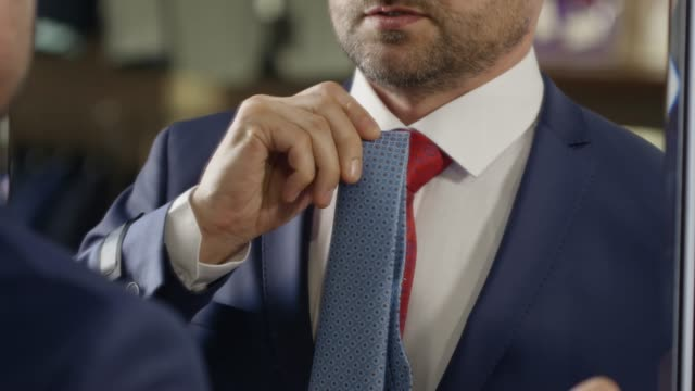 man in suit trying on neckties in store - classical architecture stock videos & royalty-free footage
