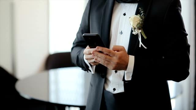 vídeos de stock, filmes e b-roll de homem de terno usando seu telefone para rede social. noivo digitando massagem para a noiva. blogs. smartphone - moda de casamento