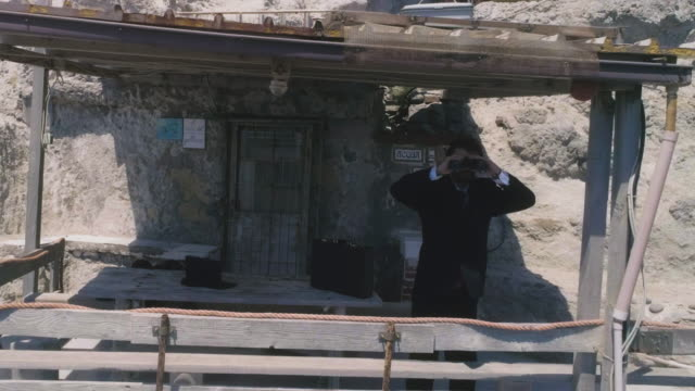 Man in suit with briefcase looks at the ocean with binoculars from a balcony on an island video