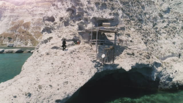 Man in suit with briefcase walking up stone steps while talking on his smartphone on an island in front of the ocean, towards wooden balcony video