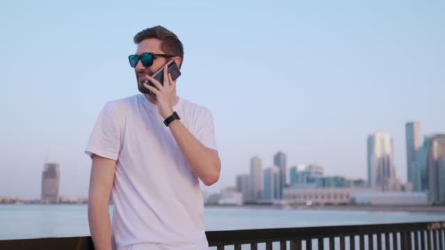 a man in summer sunglasses talking on the phone - maglietta bianca video stock e b–roll