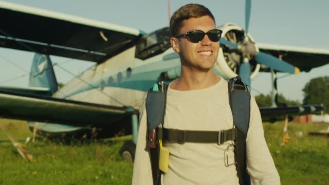 vidéos et rushes de lunettes de soleil homme marche sur l'aérodrome - parachutisme
