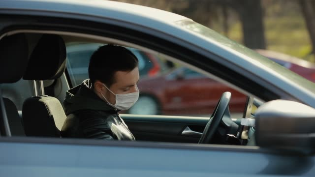 Man in surgical mask sit down in a car video