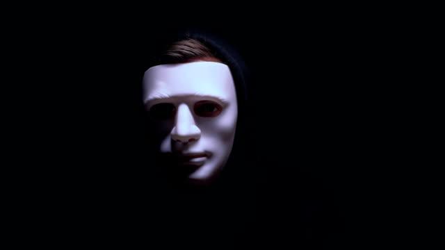 vídeos de stock e filmes b-roll de man in terrible face mask staring at camera against dark background, terrorism - capuz