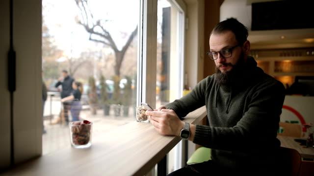 cep telefonunu kullanarak kafede adam ve onun burnunu seçmenize - burun vücut parçaları stok videoları ve detay görüntü çekimi