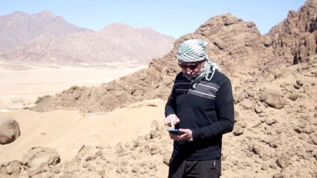 Mann in der Wüste berührt sein Smartphone – Video