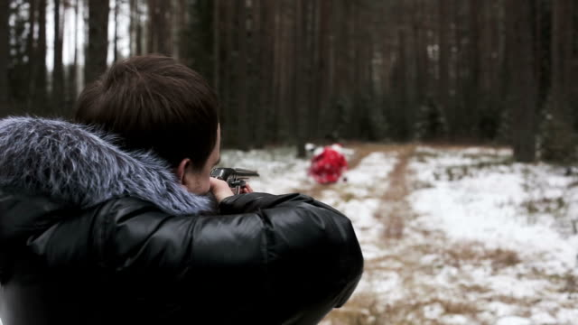 Man in the forest aiming a rifle in Santa Claus video