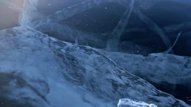 vídeos de stock, filmes e b-roll de homem nas luvinhas torce o gelo no gelo. câmera lenta. a câmera se move para trás o gelo. um pedaço de gelo é muito belamente girando no gelo com rachaduras mágicos. - temas fotográficos