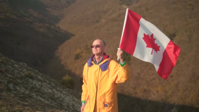 a man in the mountains stands and holds the canadian flag. he is wearing bright yellow clothes and glasses. - canada day stock videos & royalty-free footage