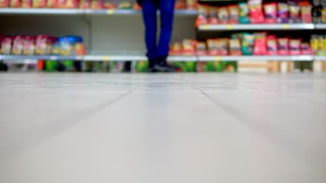 en man i butiken bär en kundvagn med mat - dagligvaruhandel, hylla, bakgrund, blurred bildbanksvideor och videomaterial från bakom kulisserna