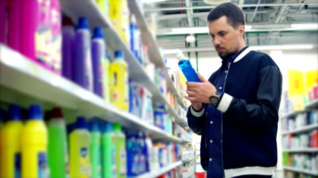 man in the store reading a label on detergent - disinfectant stock videos & royalty-free footage