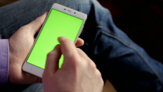 stockvideo's en b-roll-footage met man op de werkplek met behulp van zijn smartphone met groen scherm scrollen nieuws, financiële verslagen te controleren, te tikken op het scherm. handen boven weergave.  4k handen met zakelijke financiën slimme telefoon chrome sleutel - cell phone toilet