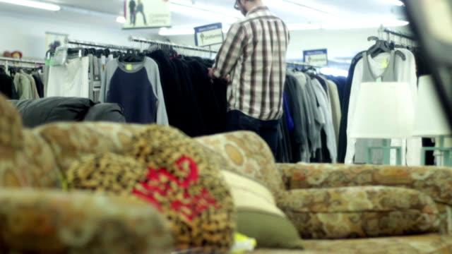 vídeos de stock, filmes e b-roll de homem em lojas de loja do thrift para algumas camisas novas - arméria