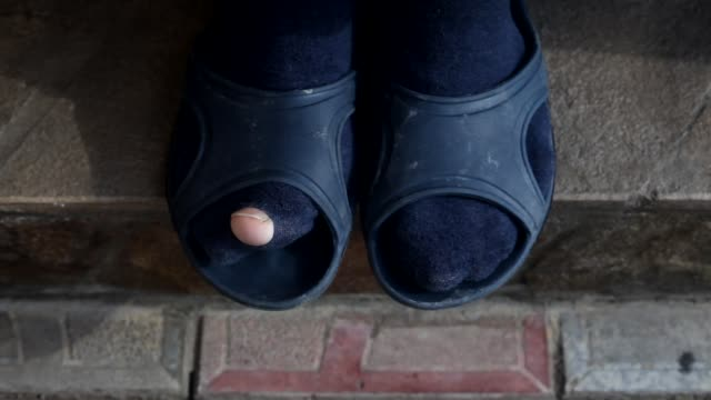 A man in torn socks and rubber slippers funny moves his finger. Man wearing blue socks with hole. Socks of a poor man.