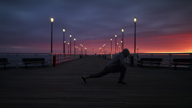 Man In Tracksuit Stretching on a Seaside Pier at Dusk - Wide Shot in 4K.