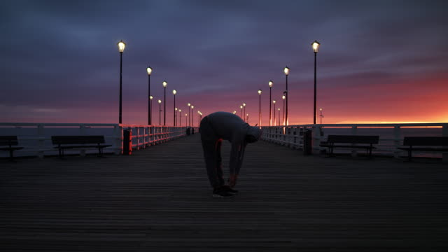 Man In Tracksuit Stretching on a Seaside Pier at Dusk - Wide Slow Motion Shot in 4K.