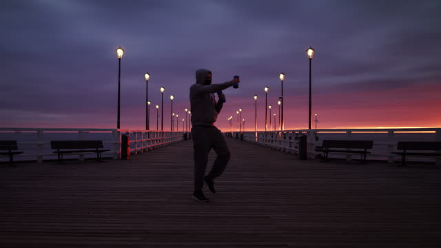 Man In Tracksuit Training with Weights on a Seaside Pier at Dusk - Wide Slow Motion Shot in 4K.