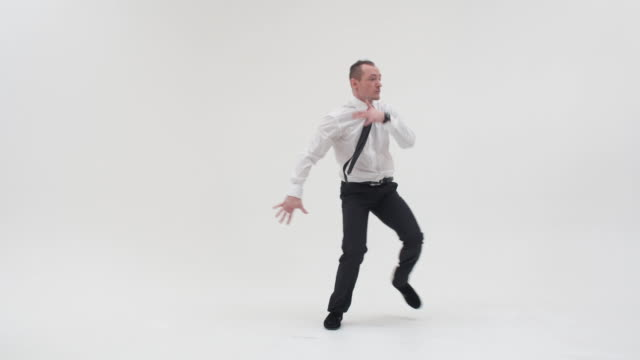 A man in trousers and a shirt dances the top break, stands on one hand spreading his legs, and with the other hand covers the groin. Office worker dancing break dance