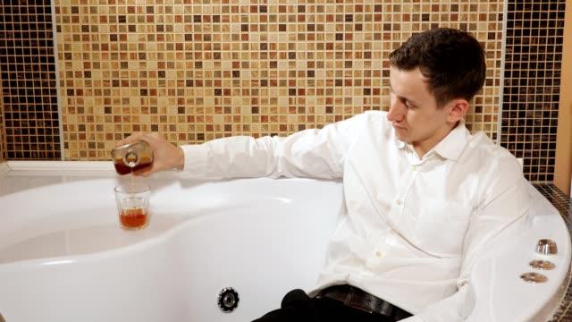 mann in hose und hemd liegt im bad und trinkt alkohol - unterordnung stock-videos und b-roll-filmmaterial