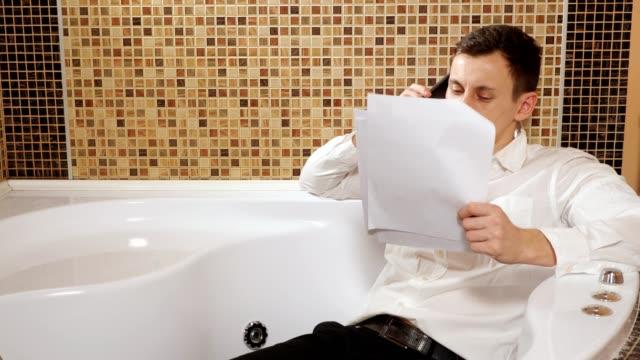 mann in hose und hemd liegt in der badewanne und telefoniert - unterordnung stock-videos und b-roll-filmmaterial