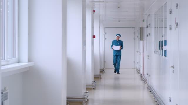 человек в форме носить белую бумагу в коридоре. рабочий-мужчина с кучей бумаги - элемент здания стоковые видео и кадры b-roll