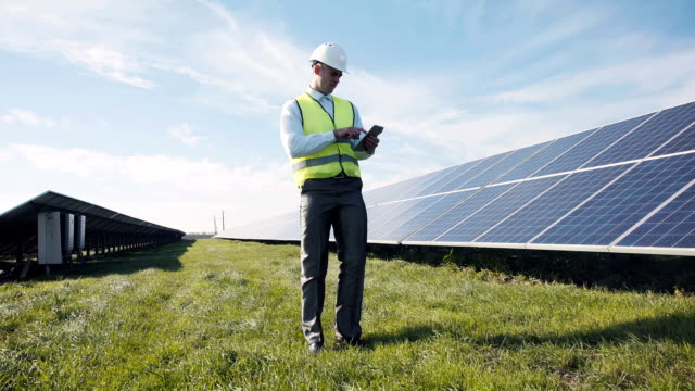 Man in vest walking near solar panels Single man in reflective green vest and white hard hat with digital tablet, walking near solar panels for concept about employment in alternative energy homegrown produce stock videos & royalty-free footage