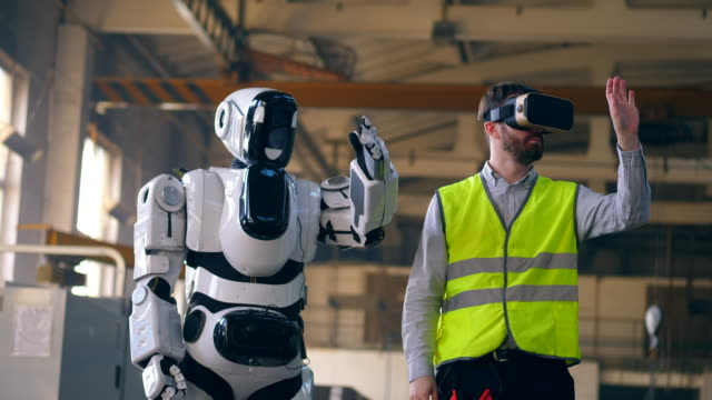 Man in VR-glasses and a cyborg are moving together