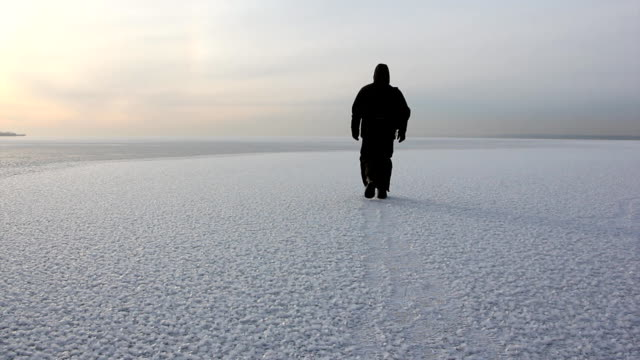 man in warm clothes walking on a frozen river at sunset, ob reservoir, siberia, russia - trekking sul ghiaccio video stock e b–roll