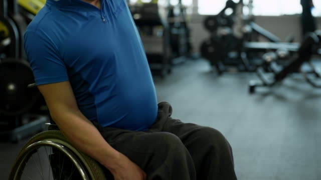 vídeos y material grabado en eventos de stock de hombre en silla de ruedas hacer ejercicio con pesas rusas en gimnasio - deportes en silla de ruedas