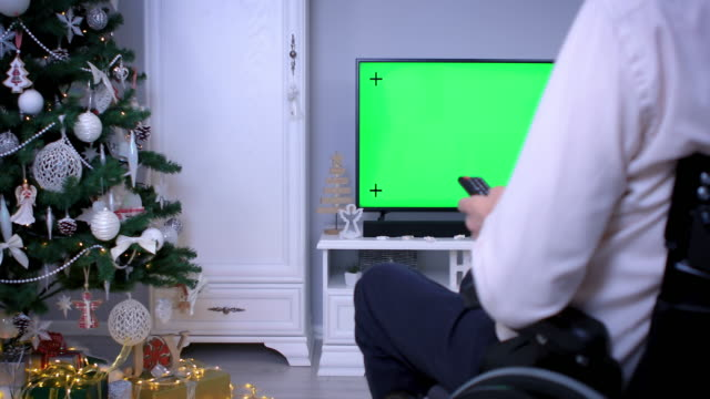 man in wheelchair watching tv green screen on christmas - christmas movie video stock e b–roll