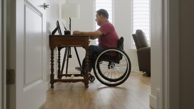 vídeos de stock e filmes b-roll de man in wheelchair working in a home office - capacidades diferentes