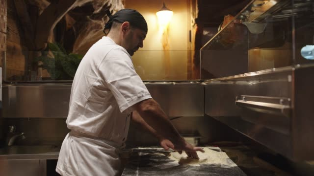 Man in white apron and chef hat using his hands to form the pizza dough video