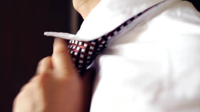 vídeos y material grabado en eventos de stock de hombre de camisa blanca, atar una corbata en la vista de perfil. 3840 x 2160 - corbata