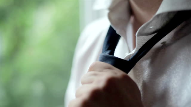 Man in white shirt tying a tie near the window. Close-up video
