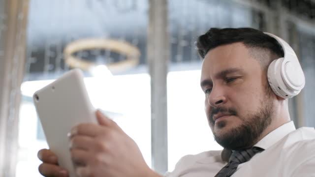 man i trådlösa hörlurar med tablet - endast en medelålders man bildbanksvideor och videomaterial från bakom kulisserna