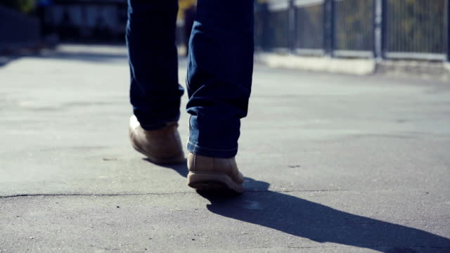 Man in yellow boots walks throughout urban environment video