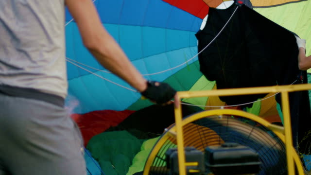 A man inflates the envelope of their hot air balloon on meadow video