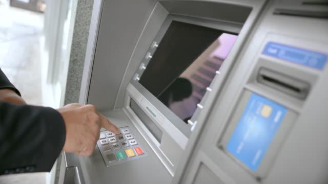 vídeos de stock, filmes e b-roll de homem de ld inserindo o cartão bancário no slot de atm e inserindo seu número pin para fazer um levantamento - pin