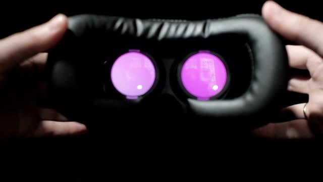 adam bir smartphone sanal gerçeklik kask içinde ekler ve gözlere getiriyor. kumar bağımlılığı. - sanal gerçeklik stok videoları ve detay görüntü çekimi