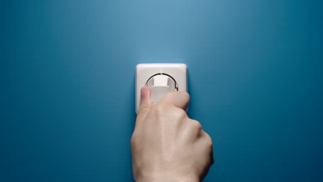 Man Inserts Plug Into Electrical Socket On A Blue Wall Man Inserts Plug Into Electrical Socket On A Blue Wall household fixture stock videos & royalty-free footage