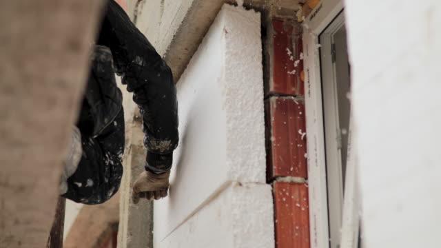 man installing styrofoam insulation board for energy saving on exterior wall of house - poliuretano polimero video stock e b–roll